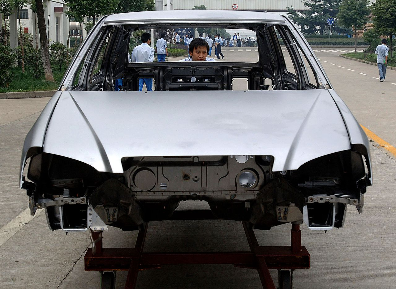 De carrosserie van een Chery wordt naar de assemblagehal geduwd in Wuhu. Chery wil gaan exporteren naar Europa en de VS. Foto AFP A Chinese worker pushes a bodyframe of a Chery car to the production line at the company's plant in Wuhu, central China's Anhui province 11 October 2006. China-based Chery has been aiming to enter the massive and highly competitive US market with small, fuel-efficient cars priced 30 to 40 percent below current offerings, while analysts have warned that US consumers would be wary of buying Chinese-made vehicles because of quality concerns. CHINA OUT GETTY OUT AFP PHOTO