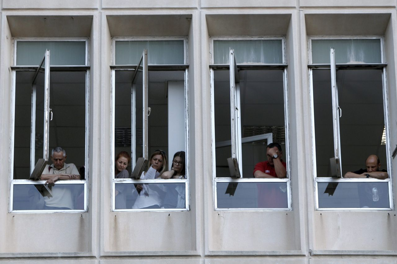Employees stand at the windows of the Greek state television (ERT) headquarters after the government's announcement that it will shut down the broadcaster in Athens June 11, 2013. Greece said it was temporarily closing state broadcaster ERT on Tuesday to lay off staff and slim down the organisation as part of budget cuts, drawing protests from workers and junior partners in the ruling coalition. REUTERS/John Kolesidis (GREECE - Tags: BUSINESS EMPLOYMENT POLITICS MEDIA TPX IMAGES OF THE DAY)