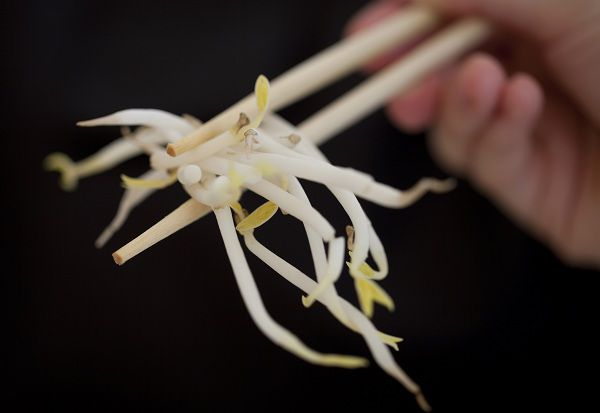 A woman holds bean sprouts with chopsticks in Berlin, Germany, Sunday, June 5, 2011. (AP Photo/Gero Breloer)