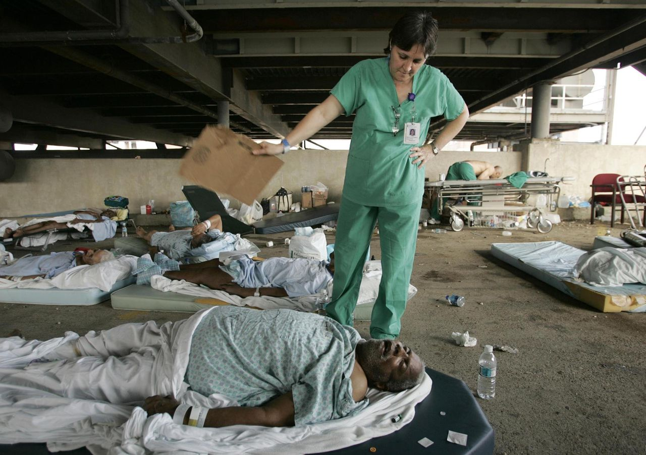 Memorial Medical Center Nurse Mary Jo D'amico fans a patient in the hospital's parking garage waiting for helicopter transport from New Orleans, Thursday, Sept. 1, 2005, in the wake of Hurricane Katrina. (AP Photo/The Dallas Morning News, Brad Loper) ** MANDATORY CREDIT: NO SALES, MAGS OUT, TV OUT, INTERNET: AP MEMBERS ONLY **