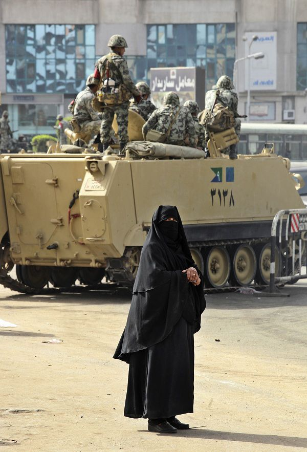 An Egyptian woman walks past Egyptian army soldiers atop armoured personnel carriers, in Cairo, Egypt, Saturday, Jan. 29, 2011. (AP Photo/Victoria Hazou)
