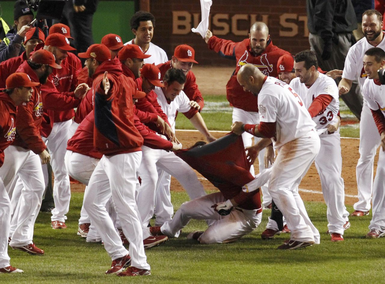 St. Louis Cardinals' David Freese has his jersey ripped off by teammates after hitting the game winning home run against the Texas Rangers in the eleventh inning in Game 6 of MLB's World Series baseball championship in St. Louis, Missouri, October 27, 2011. REUTERS/Jim Young (UNITED STATES - Tags: SPORT BASEBALL)