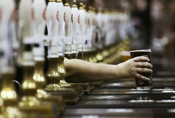 A pint of beer is served through rows of beer pumps at the Campaign For Real Ale Great British Beer Festival at Earls Court in London August 2, 2011. British pubs -- closing at record rates in a harsh economic climate -- could be saved by reviving traditional games like skittles and darts, according to a report on Tuesday. Such games have disappeared from many pubs in recent years in favour of gaming machines which charge customers to play, and from which landords can take a cut, the report said. To match Reuters Life! BRITAIN-PUBS/ REUTERS/Luke MacGregor (BRITAIN - Tags: BUSINESS IMAGES OF THE DAY SOCIETY)