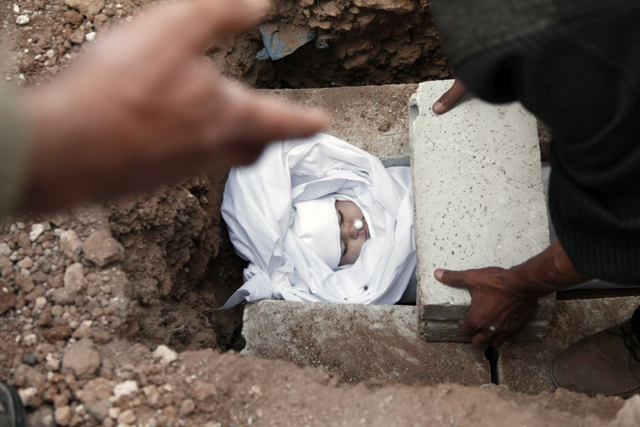 Syrians and Jordanians bury the body of Emara al-Zoabi, 7-months-old, who was killed from Syrian government forces shelling in Ramtha City, north Amman, Jordan, Sunday, Dec. 2, 2012. Al-Zoabi was killed in Tafas village, in the Syrian city of Daraa, on Dec. 1. (AP Photo/Mohammad Hannon)