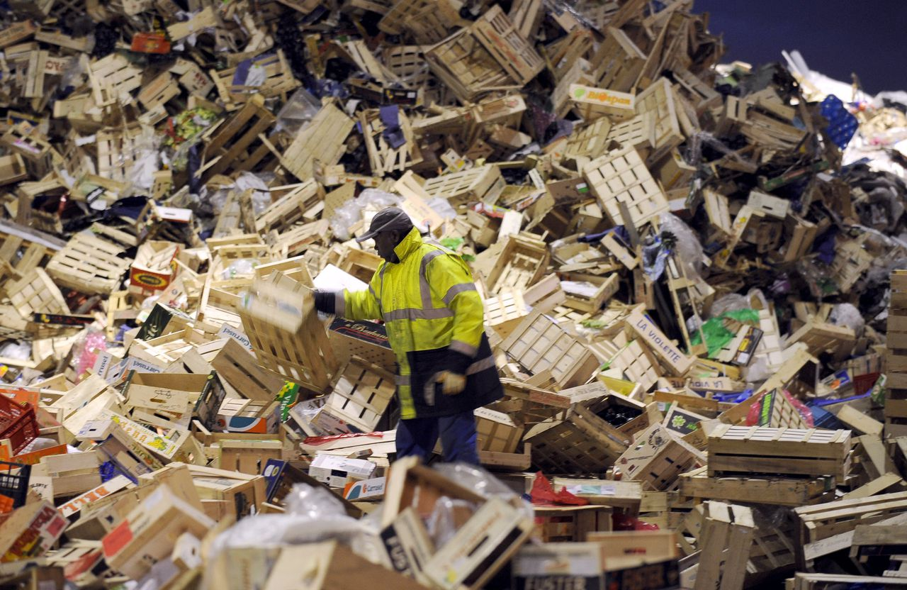 A man works with wood boxes in the selective sorting area of the Rungis international food market on December 1, 2009 in Rungis, near Paris. Rungis international market is Europe biggest wholesale food market and 18 million European consumers are supplied from here, including 12 million within a radius of 150 km around Paris. AFP PHOTO FRED DUFOUR