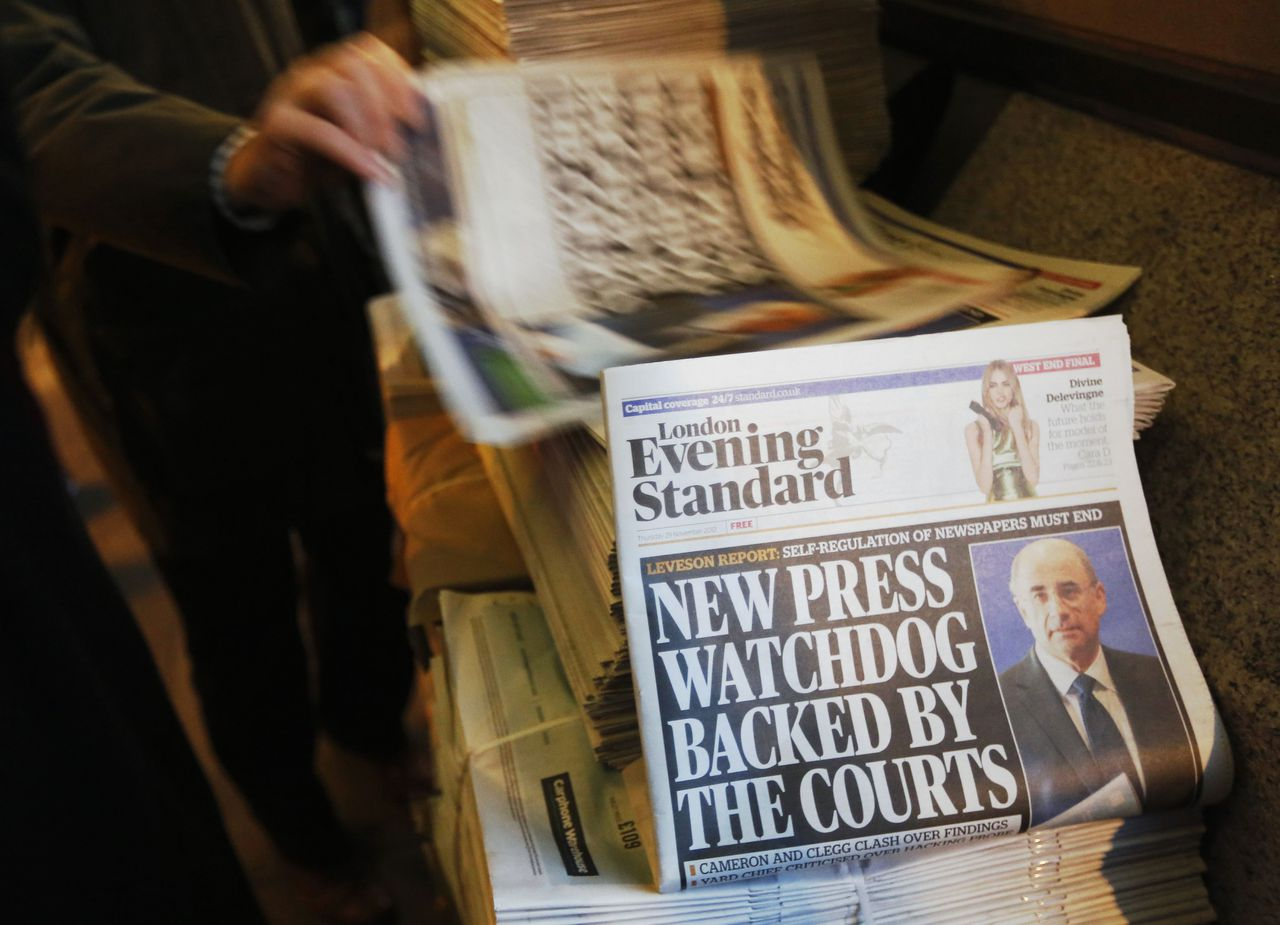 Lord Justice Brian Leveson appears on the front page of a stack of evening newspapers after his report on media practices was released in central London November 29, 2012. British Prime Minister David Cameron said on Thursday that he had serious concerns about legislation to regulate the media, risking a split in his coalition after a damning inquiry triggered by a phone-hacking scandal proposed a press watchdog backed in law. REUTERS/Luke MacGregor (BRITAIN - Tags: POLITICS MEDIA CRIME LAW)