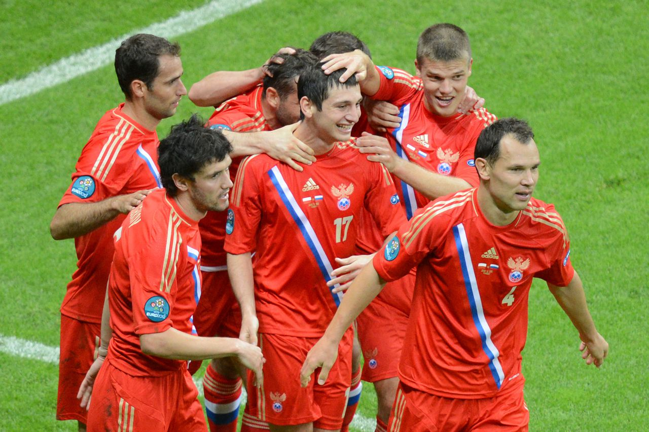 Russian midfielder Alan Dzagoev (C) celebrates with teammates after scoring during the Euro 2012 championships football match Poland vs Russia on June 12, 2012 at the National Stadium in Warsaw. AFP PHOTO / DIMITAR DILKOFF