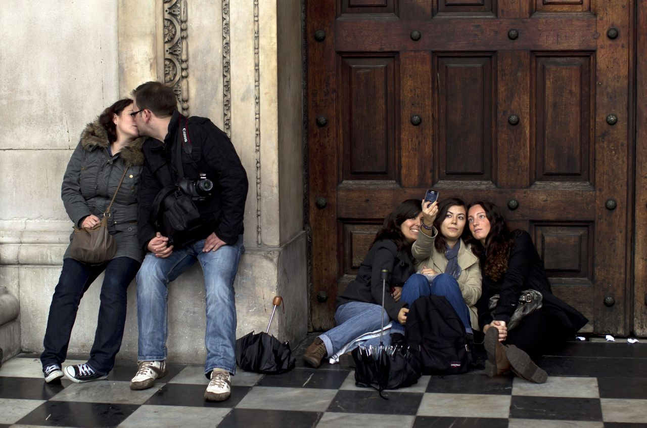 French tourists take a photo of themselves as a couple kiss outside the main front door, that usually remains locked except for special events, of St Paul's Cathedral in London, Thursday, Oct. 27, 2011. St. Paul's Cathedral says it will reopen Friday, a week after is shut its doors because of an anti-capitalist protest camp outside. It will reopen to tourists on Saturday. Protesters have been camped outside the building since Oct. 15. Days later, cathedral officials shut the building to the public, saying the campsite was a health and safety hazard. (AP Photo/Matt Dunham)