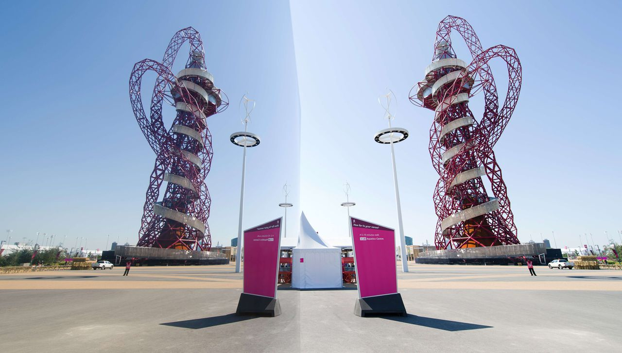 The ArcelorMittal Orbit sculpture (R) by British artist Anish Kapoor (R) is reflected in a polished art installation within the Olympic Park in London on July 23, 2012. The London 2012 Olympic Games begin on July 27, 2012. AFP PHOTO / LEON NEAL