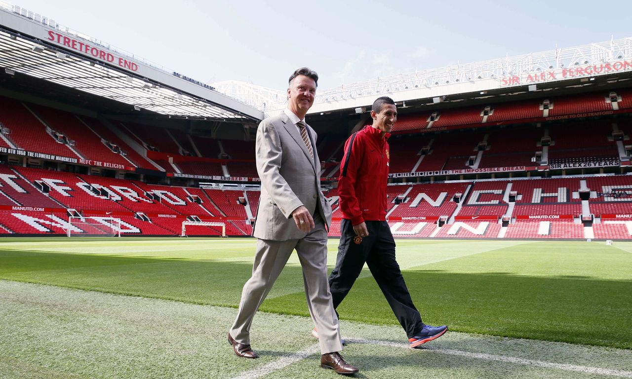 Manchester United's new player Angel Di Maria centre right, and manager Louis van Gaal, pose for photographers walk towards a photo call, at Old Trafford Stadium in Manchester, England, Thursday, Aug. 28, 2014. Manchester United have signed winger Angel Di Maria from Real Madrid for a British record transfer fee of £59.7m. The Argentine winger had a medical in Manchester on Tuesday and has signed a five-year deal. (AP Photo/Alastair Grant)
