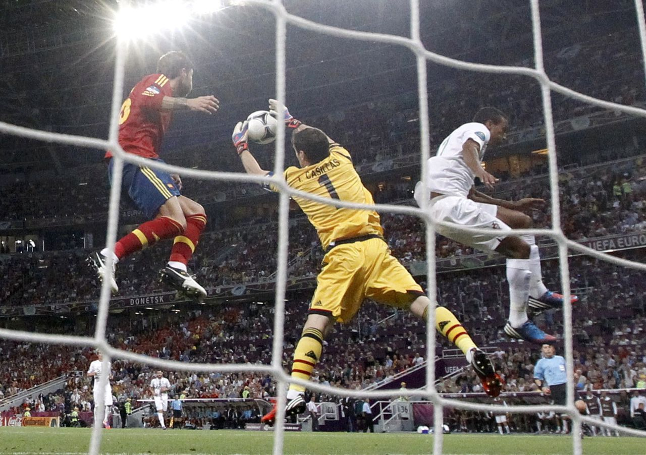 Spain's goalkeeper Iker Casillas (C) makes a save next to team mate Andres Iniesta (L) and Portugal's Nani during their Euro 2012 semi-final soccer match at the Donbass Arena in Donetsk, June 27, 2012. REUTERS/Alessandro Bianchi (UKRAINE - Tags: SPORT SOCCER)