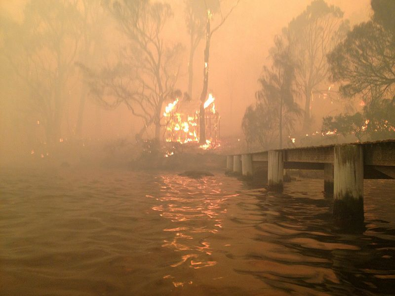In this Jan. 4, 2013, photo provided by the Holmes family a building burns near a jetty where Tim and Tammy Holmes are sheltering under a jetty with their five grandchildren as a wildfire rages near-by at Dunalley, Australia. The family credits God with their survival from the fire that destroyed around 90 homes in Dunalley. (AP Photo/Tim Holmes) Editorial Use Only
