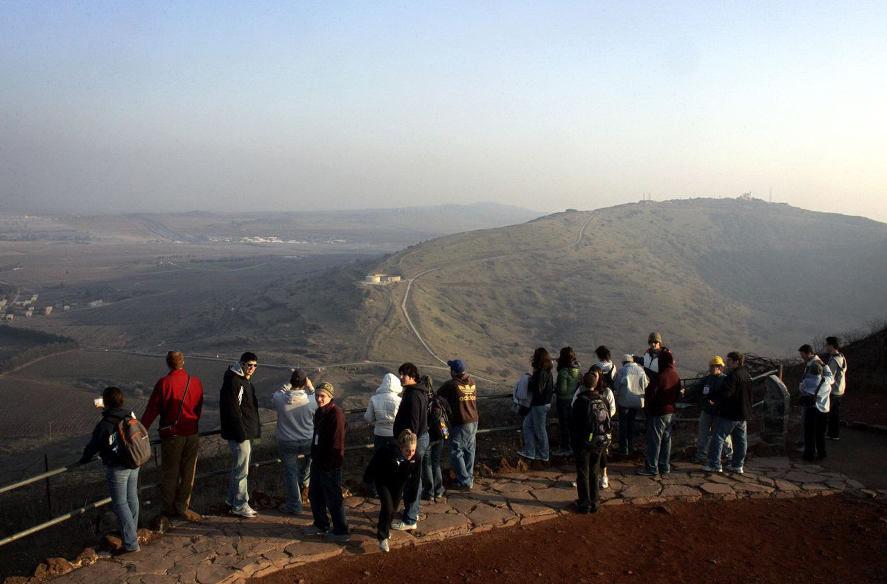 Toeristen staan in een verlaten legerkamp in de Golan-hoogvlakte en kijken naar de grens van Syrië. Foto AFP Tourists look out towards Syria at an abandoned army post from the 1967 war in the Golan Heights, 16 January 2007. Israelis and Syrians reached understandings for a peace treaty in secret unofficial talks over the past two years, the Israeli daily Haaretz reported today, but both governments denied knowledge of the contacts. Under the agreement, Israel would withdraw from all of the strategic Golan Heights that it captured from Syria in the 1967 Six Day War and annexed in 1981. AFP PHOTO/DAVID FURST