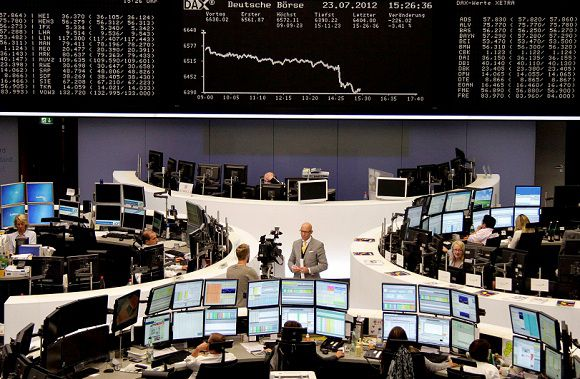 Caption: Traders are pictured at their desks in front of the DAX board at the Frankfurt stock exchange, July 23, 2012. REUTERS/Remote/Michael Leckel (GERMANY - Tags: BUSINESS)