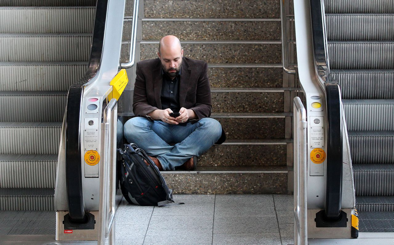 A stranded passenger uses his mobile device as he sits on stairs in a terminal at the international airport in Frankfurt, Germany, Tuesday, March 27, 2012. More than 400 flights had to be cancelled when ground staff organized in the German ver.di union went on a warning strike for higher wages until the afternoon.(AP Photo/Michael Probst)