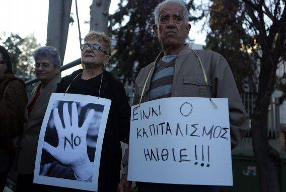 Demonstranten protesteren buiten bij het parlementsgebouw van Cyprus tegen het steunplan van de eurolanden voor het eiland, dat onder meer een spaardersheffing omvat. Op het protestbord rechts staat: 'Het is kapitalisme idioten!'