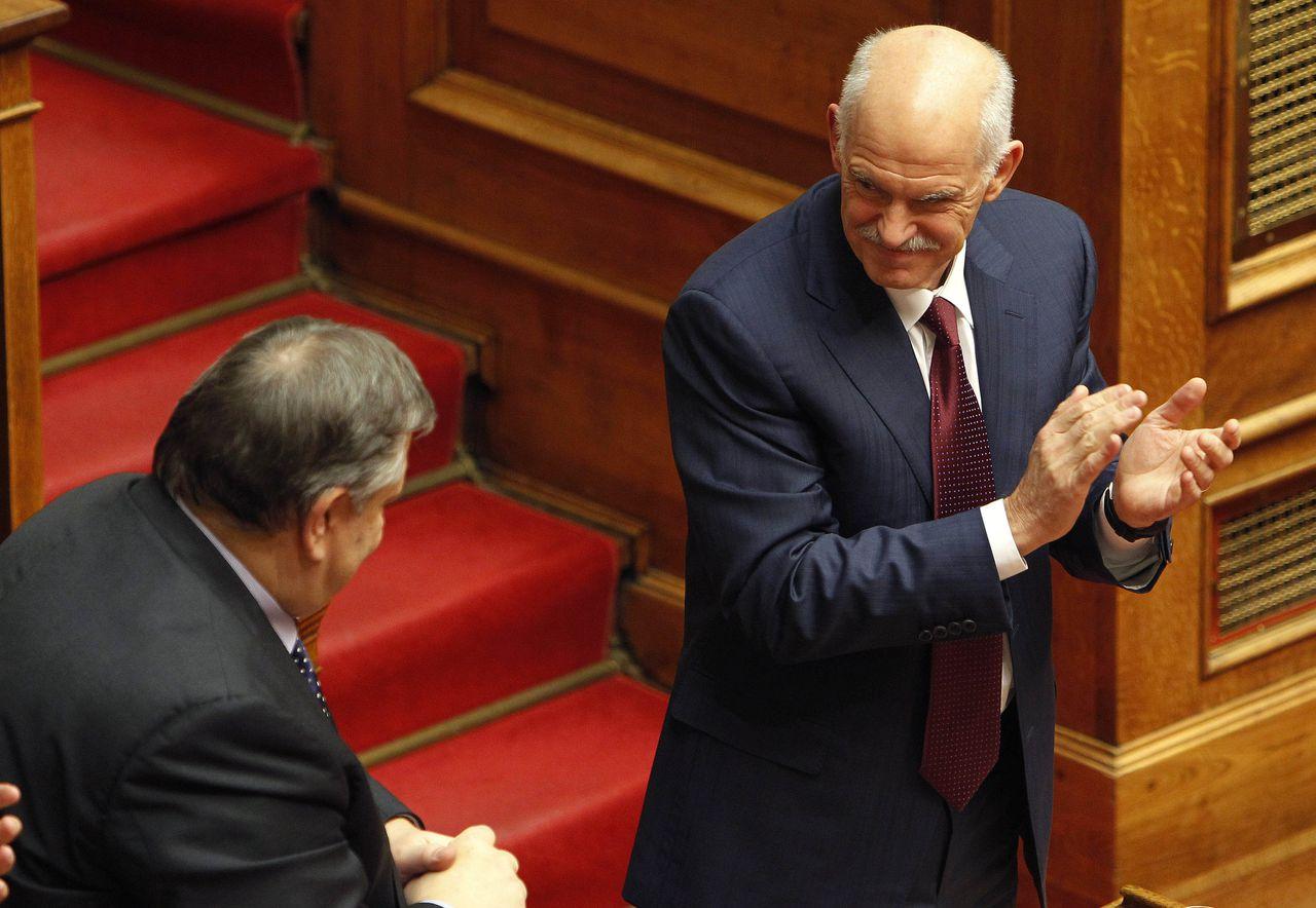 Greek Prime minister George Papandreou applauds as he looks Finance Minister Evangelos Venizelos after confidence vote at the parliament in Athens, early Saturday, Nov. 5, 2011. Greece's prime minister has survived a confidence vote in parliament, calming a revolt in his Socialist party with a pledge to seek an interim government that would secure a vital new European debt deal. (AP Photo/Thanassis Stavrakis)