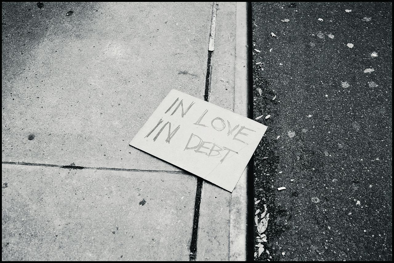 """USA. New York City. 17 November 2011. A disgarded Occupy Wall Street sign lies on the ground following arrests near Wall Street. It reads, """"In Love In Debt"""" Contact email: New York : photography@magnumphotos.com Paris : magnum@magnumphotos.fr London : magnum@magnumphotos.co.uk Tokyo : tokyo@magnumphotos.co.jp Contact phones: New York : +1 212 929 6000 Paris: + 33 1 53 42 50 00 London: + 44 20 7490 1771 Tokyo: + 81 3 3219 0771 Image URL: http://www.magnumphotos.com/Archive/C.aspx?VP3=ViewBox_VPage&IID=2K7O3RKWR6VO&CT=Image&IT=ZoomImage01_VForm"""