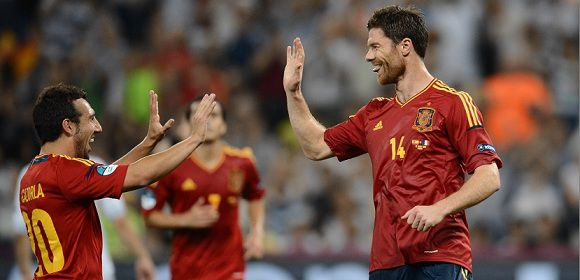 Caption: Spanish midfielder Xabi Alonso (R) celebrates with midfielder Santi Cazorla after he scored a goal during the Euro 2012 football championships quarter-final match Spain vs France on June 23, 2012 at the Donbass Arena in Donetsk. AFP PHOTO / FRANCK FIFE