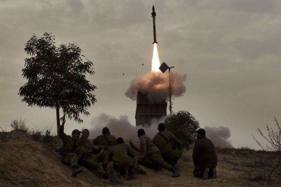 Israeli soldiers watch as a missile is launched from the Iron Dome defence system in the southern Israeli city of Beer Sheva on March 12, 2012, as a new round of tit-for-tat violence between Gaza militants and Israel has ruptured the calm that was restored after a major flare-up last August. AFP PHOTO/MENAHEM KAHANA