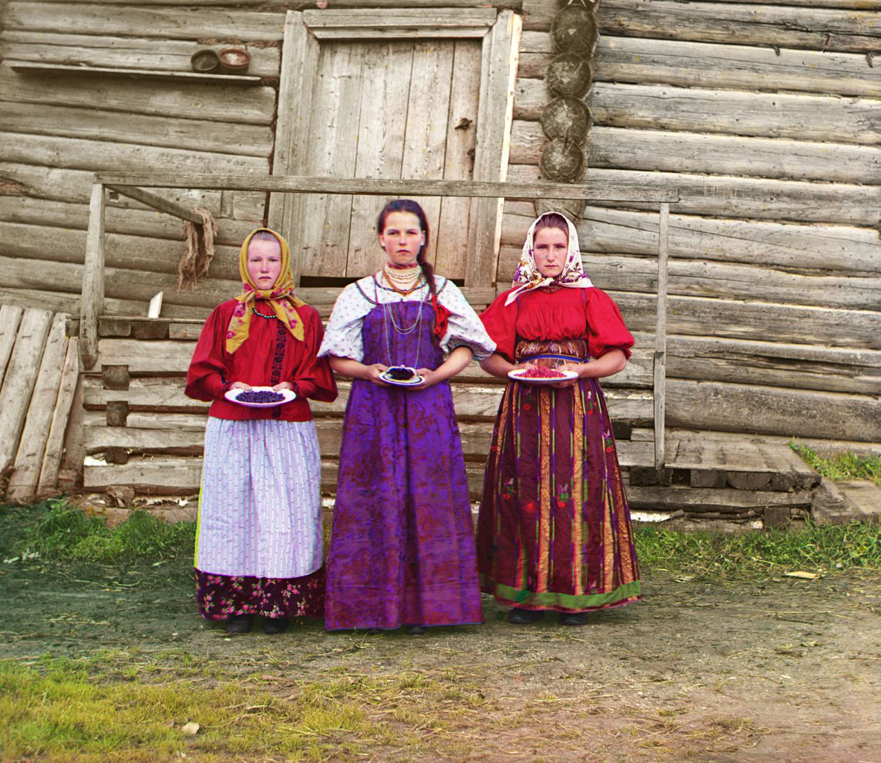 Russian peasant girls offer berries to visitors to their izba, a traditional wooden house, in a rural area along the Sheksna River near the small town of Kirillov, Russia, 1909. (Photo by Sergey Prokudin-Gorsky/Galerie Bilderwelt/Getty Images)