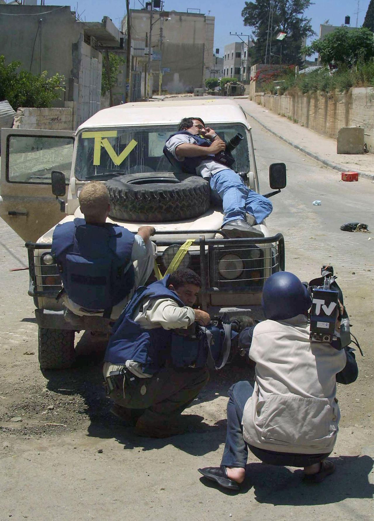 Buitenlandse en Palestijnse journalisten zoeken dekking voor Israëlisch vuur in Tulkarem in mei 2002. Foto AFP/Jaafar Ashtiyeh Foreign and local Palestinian journalists take cover behind an armored vehicle as Israeli troops fire towards them from an armored personnel carrier (background R) down a street in the town of Tulkarem 25 May 2002. The Israeli army continued raids in the autonomous Palestinian area of the West Bank following a series of suicide bomb attacks earlier in the week. Palestinian security sources said that Israel has detained about 100 Palestinians in the incursion. AFP PHOTO/Jaafar ASHTIYEH