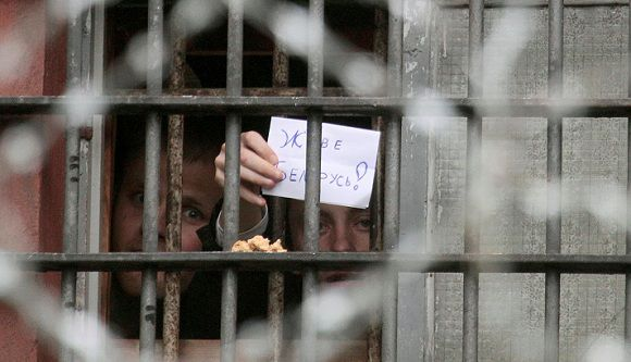 """Caption: Belarusian detainees, arrested during the flash mob dubbed """"Revolution through a social network"""", hold a piece of paper which reads """"Long live Belarus"""", at a detention centre in Minsk July 6, 2011. Belarus's """"clapping"""" protesters defiantly announced new street action against President Alexander Lukashenko on Monday despite a crackdown by police in which more than 300 people may have been arrested, local media reported. REUTERS/Vasily Fedosenko (BELARUS - Tags: POLITICS CRIME LAW CIVIL UNREST)"""