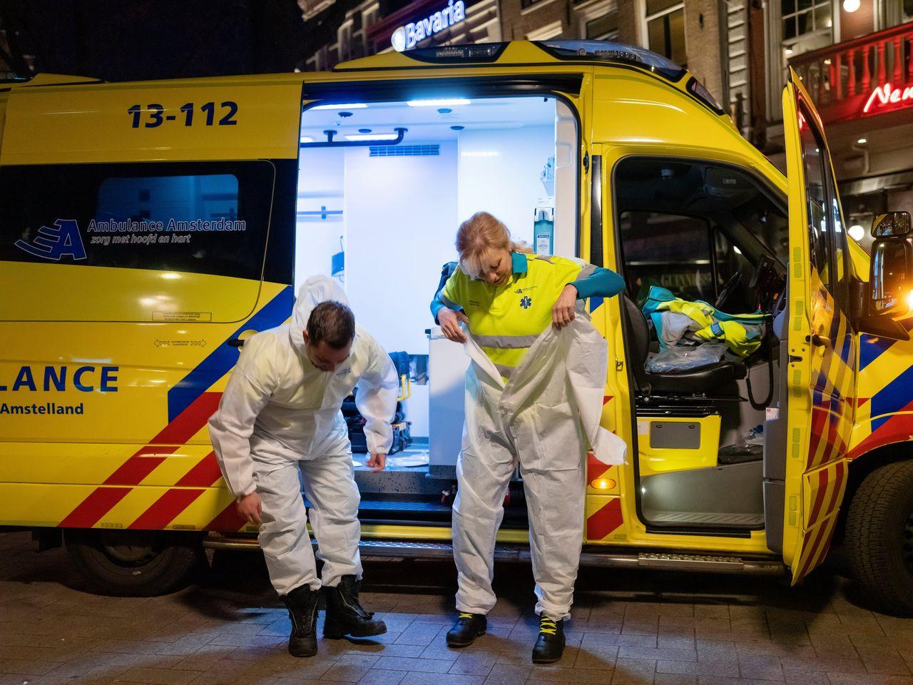 Hans Schuitmaker en Annemiek Valent van Ambulance Amsterdam trekken hun Covidpak aan.