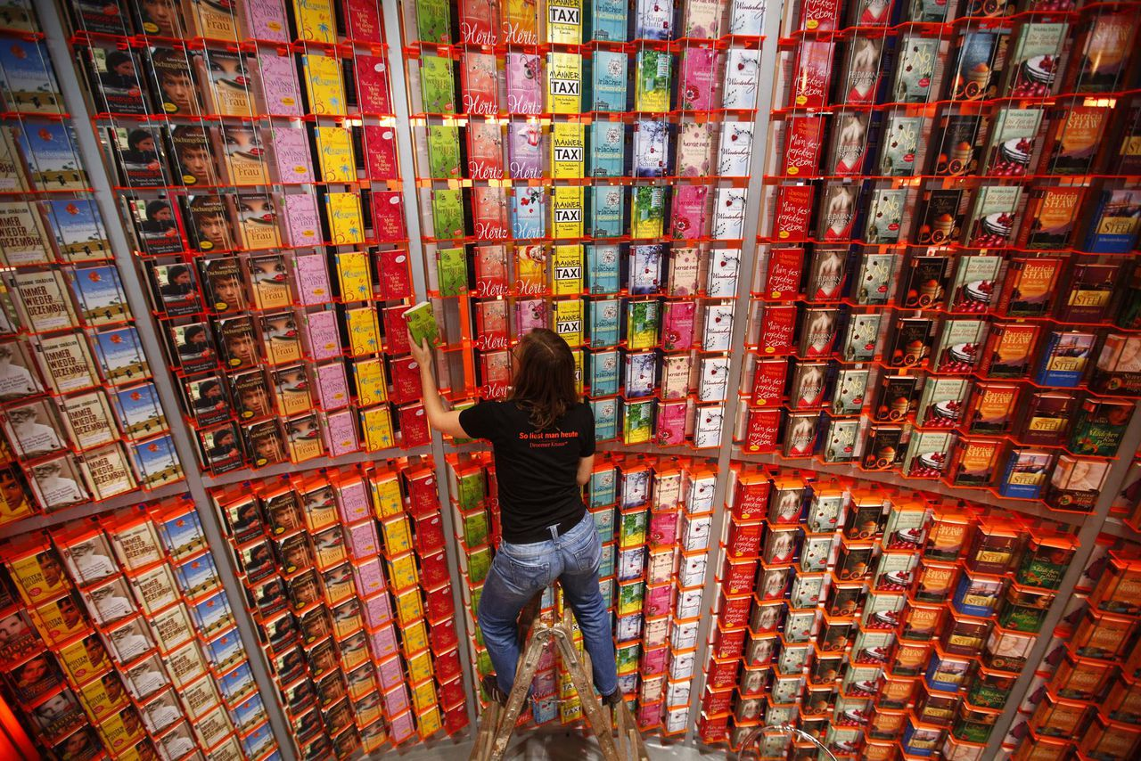 Sylvia Fleischer of German publishing house Droemer Knaur makes final adjustments on a huge bookshelf prior to the opening of the book fair in Frankfurt, October 5, 2010. The world's largest book fair, which will be officially opened by Argentinian President Cristina Fernandez de Kirchner later today, runs until October 10. Argentina is the guest of honour. REUTERS/Kai Pfaffenbach (GERMANYENTERTAINMENT MEDIA BUSINESS - Tags: EDUCATION SOCIETY IMAGES OF THE DAY) ENTERTAINMENT MEDIA BUSINESS)