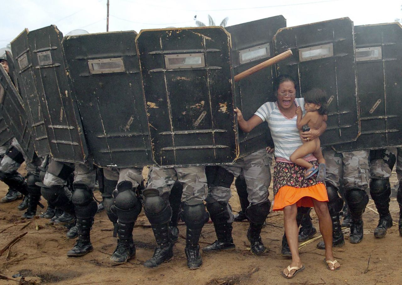 Actie tegen boeren die zich land hebben toegeëigend in het Amazonegebied, Brazilië, 11 maart 2008 Reuters, Luis Vasconcelos An indigenous woman holds her child while trying to resist the advance of Amazonas state policemen who were expelling the woman and some 200 other members of the Landless Movement from a privately-owned tract of land on the outskirts of Manaus, in the heart of the Brazilian Amazon March 11, 2008. The landless peasants tried in vain to resist the eviction with bows and arrows against police using tear gas and trained dogs. REUTERS/Luiz Vasconcelos-A Critica/AE (BRAZIL). FOR EDITORIAL USE ONLY. NOT FOR SALE FOR MARKETING OR ADVERTISING CAMPAIGNS.. BRAZIL OUT. NO COMMERCIAL OR EDITORIAL SALES IN BRAZIL..