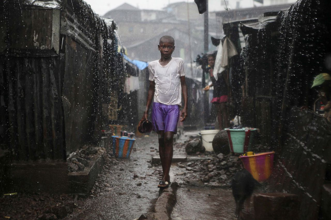 "A child stands in pouring rain in the slum of Susan's Bay in Sierra Leone's capital Freetown, August 22, 2012. Sierra Leone's government has described the current cholera outbreak in the West African state as a ""national emergency."" At the height of the wet season, over-populated areas with poor water and sanitation are exacerbating the spread of the disease. Some 170 deaths are reported since the start of the year. Picture taken August 22, 2012. REUTERS/Simon Akam (SIERRA LEONE - Tags: HEALTH ENVIRONMENT TPX IMAGES OF THE DAY)"