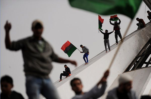 "Residents of the north central town of Benghazi wave an old Libyan flag as others celebrate burning books authored by Libyan ruler Moamer Kadhafi at a local park in the city on March 02, 2011. Kadhafi warned the West on Wednesday against intervening to support the rebellion against him, saying that would unleash a ""very bloody war"" in which ""thousands of Libyans would die."" Speaking live on state television, Kadhafi again blamed Al-Qaeda for the challenge to his 41-year iron-fisted rule, saying the objective was to control Libya's land and oil and promising to fight to the last man and woman. TOPSHOTS / AFP PHOTO / ROBERTO SCHMIDT"