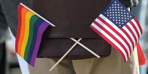 Caption: SAN FRANCISCO, CA - JUNE 13: A gay pride and an American flag hang from a shoulder bag during a demonstration outside of the Phillip Burton Federal Building on June 13, 2011 in San Francisco, California. Sponsors of Proposition 8, a California ballot measure that would deny same-sex couples to marry in the state, are back in court today to ask a federal judge to nullify U.S. District Judge Vaughn Walker's decision to overturn California's ban on same-sex marriage. Justin Sullivan/Getty Images/AFP