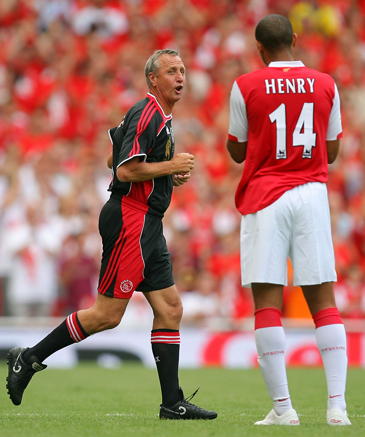 """Johan Cruijff (links) en Thierry Henry. Foto AFP Dutch soccer legend and Ajax player Johan Cruyff (L) reacts to appluse by Arsenal's Thierry Henry during a pre season """"Dennis Bergkamp"""" testimonial match at Emirates stadium in north London, 22 July 2006.The match played in honour of Arsenal's Dutch player Dennis Bergkamp who has served the club for 11 years and will retire after the game is the first match played at the club's new stadium.Arsenal defeated Ajax 2-1. AFP PHOTO / ODD ANDERSEN"""