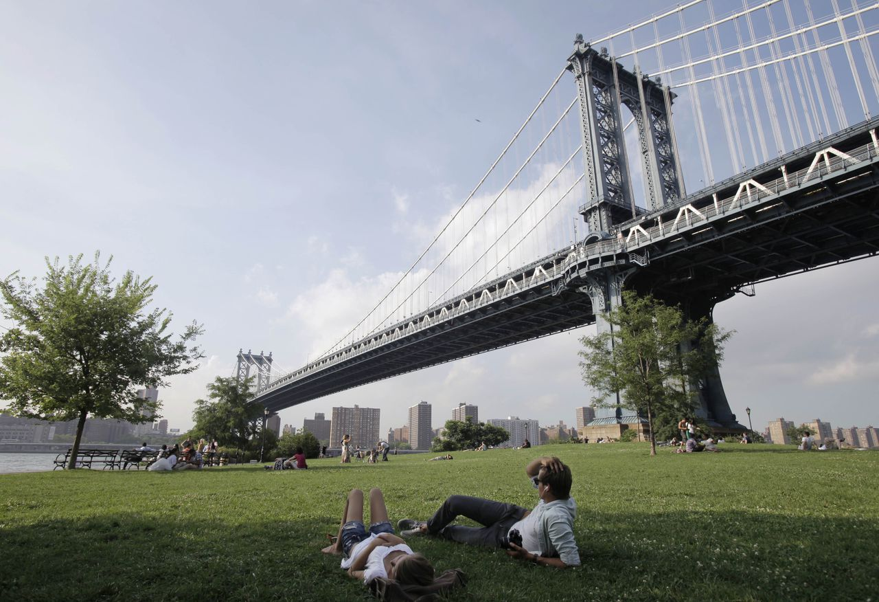 FILE - In this file photo of July 15, 2010, a couple relaxes in Brooklyn Bridge Park beneath the Manhattan Bridge in New York. The city's first waterfront plan in two decades is to be announced Monday, March 14, 2011. The blueprint is New York's attempt to reverse more than a century of planning that left much of the city's 520 miles of shoreline inaccessible to residents and instead directed them inland for their recreation and relaxation. (AP Photo/Kathy Willens, file)