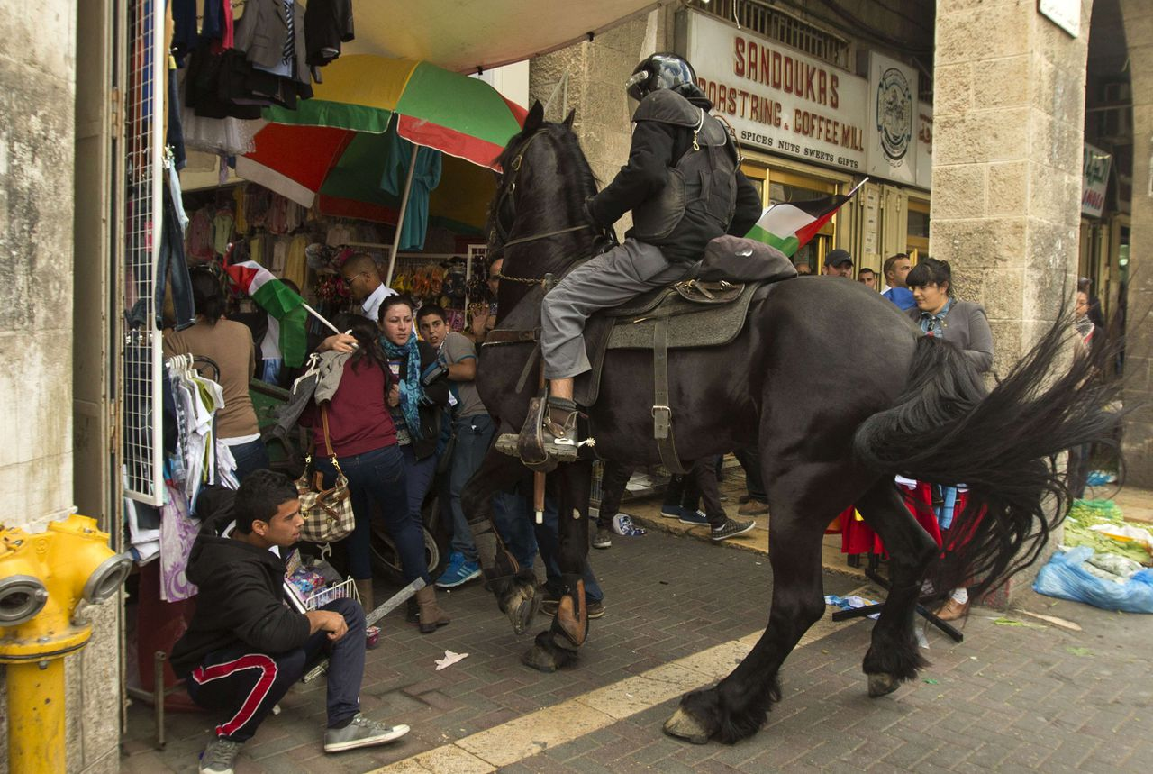"A mounted Israeli policeman tries to disperse Palestinian protestors waving their national flag during clashes as demonstrators gathered outside Damascus gate in Jerusalem on May 15, 2013 to mark the 65th Nakba or ""catastrophe"" of the Jewish state's creation in 1948, during which 760,000 Palestinians fled their homes. Thousands of Palestinians took to the streets in the West Bank and the Gaza Strip to demonstrate on Nakba Day and assert their ""right to return"" to where their ancestors fled after the Israeli victory over Arab armies. AFP PHOTO / JACK GUEZ"