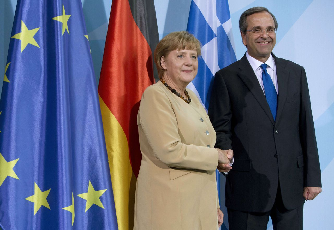 (FILES) Photo taken on August 24, 2012 shows German Chancellor Angela Merkel and Greece's prime minister Antonis Samaras shake hands after a press conference at the Chancellery in Berlin. Greece on Friday welcomed an upcoming visit to Athens by German Chancellor Angela Merkel as a step toward solving the eurozone debt crisis. AFP PHOTO / DAVID GANNON