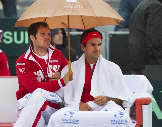 Switzerland's Roger Federer (R) and his coach Severin Luthi wait for the rain to stop during his Davis Cup tennis match against Thiemo de Bakker of the Netherlands in Amsterdam September 14, 2012. REUTERS/Paul Vreeker/United Photos (NETHERLANDS - Tags: SPORT TENNIS ENVIRONMENT)