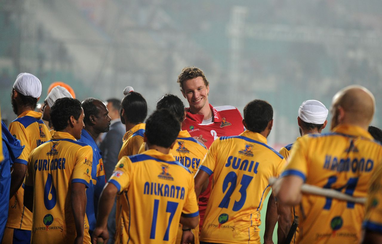 Dutch hockey goalkeeper Jaap Stockmann (C) shares a light moment with his Punjab Warriors teammates prior to the inaugural match of the Hockey India League (HIL) between Punjab Warriors and Delhi Waveriders in New Delhi on January 14, 2013. AFP PHOTO/SAJJAD HUSSAIN