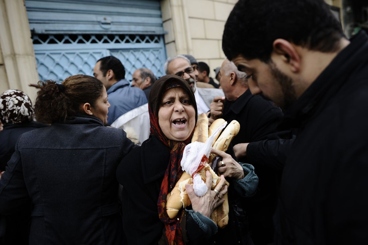 Brood kopen in de hoofdstad Tunis. De regering belooft lagere voedselprijzen, maar Tunesiërs blijven bezorgd over schaarste. Foto AFP TOPSHOTS-Tunisians buy bread in the center of Tunis on January 17, 2011. Tunisian protesters called for the abolition of ousted president Zine El Abidine Ben Ali's ruling party on January 17 amid a chaotic power vacuum as politicians prepared a government of national unity. Hundreds of people rallied in Tunis and there were similar protests in Sidi Bouzid and Regueb in central Tunisia -- two towns at the heart of the movement that forced Ben Ali to resign and flee on Friday after 23 years in power. AFP PHOTO / FRED DUFOUR