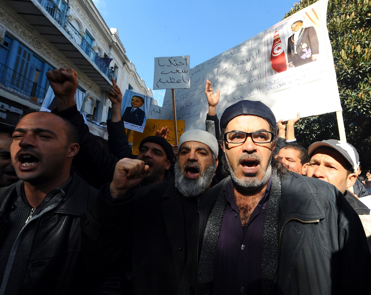 """Tunisian Muslims shout slogans after Friday prayers on January 21, 2011 in Tunis. Imams recited prayers for the """"martyrs of the revolution"""" in mosques across Tunisia on Friday a week after popular protests ended the authoritarian rule of veteran president Zine El Abidine Ben Ali. AFP PHOTO/FETHI BELAID"""