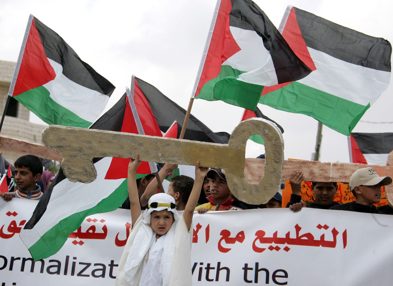 "Palestijnen vierden op 8 mei j.l. niet het 60-jarige bestaan van de staat Israël maar die van de zogenaamde Nakba (catastrofe) Foto Abbas Momani/AFP A Palestinian boy holds up a large cardboard key at the head of a procession of children waving Palestinian flags as they commemorate the 60th anniversary of the ""Nakba"" (catastrophe) and demand the right of return for refugees in the West Bank village of Bedo south of Ramallah city on May 9, 2008. As Israel celebrated its 60th birthday yesterday Palestinians are marking 60 years since the catastrophe when refugees fled their homes during the 1948 war that followed the creation of the Jewish state. AFP PHOTO/ABBAS MOMANI"