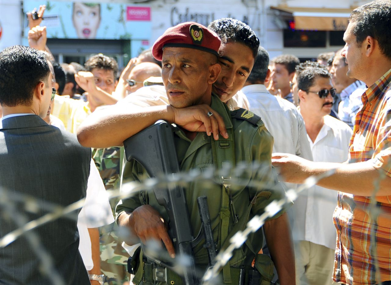 Een stakende Tunesische politieman toont zijn solidariteit met een soldaat, na een relletje in Tunis. Elke dag zijn er stakingen en protesten. Foto AP A Tunisian police officer, on strike, fraternizes with a soldier guarding the interior ministry following brief scuffles in Tunis, Tunisia, Thursday, Sept. 8, 2011. Police and security officials have been protesting in recent days in front of the Interior Ministry over perceived insults from the prime minister. Tunisia, which unleashed the Arab Spring with an uprising earlier this year, is seeing scattered protests and unrest ahead of landmark elections next month. (AP Photo/Hassene Dridi)