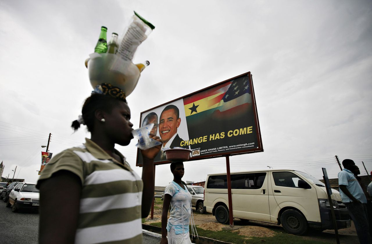 Ghana leeft massaal toe naar de komst van president Barack Obama. In de stad Cape Coast laat de Ghanese president John Atta Mills zich afbeelden met Obama. Foto Reuters A woman carries goods on her head past a billboard depicting the likenesses of Ghana's President John Atta Mills and U.S. President Barack Obama in the Ghanaian town of Cape Coast July 9, 2009. Goodwill for President Barack Obama could give the United States a little extra leverage to push good governance in Africa as well as in its priorities of securing energy supplies and fighting terrorism. As the first black U.S. president, Obama is assured of an African hero's welcome in Ghana at the weekend. REUTERS/Finbarr O'Reilly (GHANA POLITICS SOCIETY)