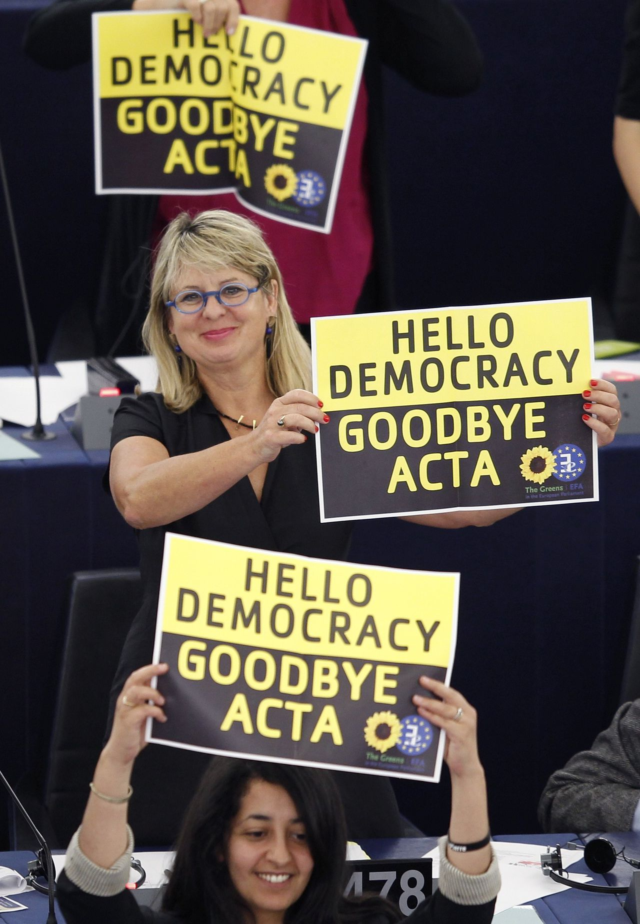 Members of the the Group of the Greens/European Free Alliance hold posters which read 'hello democracy, goodbye ACTA' during a voting session on the Anti-Counterfeiting Trade Agreement (ACTA) at the European Parliament in Strasbourg, July 4, 2012. REUTERS/Vincent Kessler (FRANCE - Tags: POLITICS)