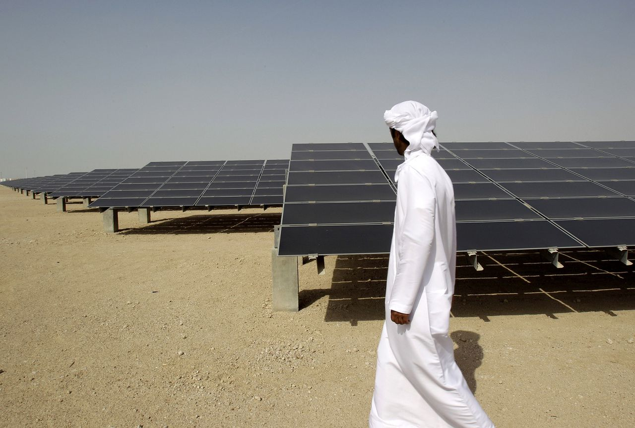 """FILE - In theis Sunday, Jan. 16, 2011 file photo, an Emirati man pass by 10mw photovoltaic plant at Masdar City in Abu Dhabi, United Arab Emirates. The dean of a research institute at the core of Abu Dhabi's green-energy city said Sunday the government remains firmly committed to renewable power after recent shifts in the ambitious project's goals. Masdar City was originally conceived as a self-contained """"carbon-neutral"""" community of 40,000 residents and even more commuters where cars would be banned and waste and water would be recycled.(AP Photo/Kamran Jebreili, File)"""