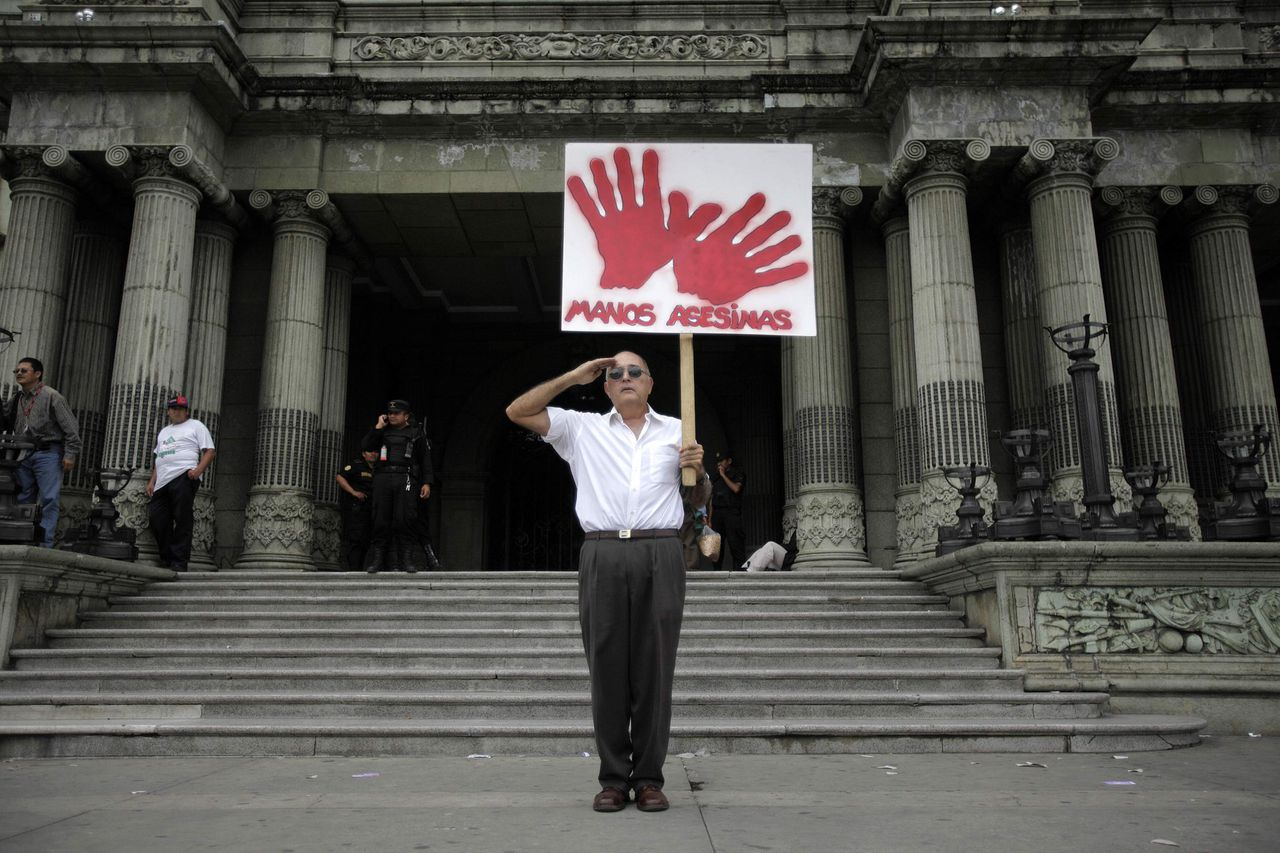 Een betoger tegen de Guatemalteekse president Álvaro Colom houdt voor het Nationaal Paleis een bord omhoog met de tekst 'moordenaarshanden', en salueert. (Foto Reuters) A protester holds a sign that reads ¨Murdering Hands¨ in front of the National Palace in Guatemala City May 15, 2009. Daily protests against Guatemala's President Alvaro Colom have been met with counter protests showing support. Colom and Guatemala's business elite are embroiled in a scandal involving money laundering, embezzling government funds and ordering assassinations, following the murder of a prominent lawyer Rodrigo Rosenberg. Copies of a video and written statement made by Rosenberg arrived at the offices of several media houses in the capital on Monday, one day after the lawyer was shot dead by armed men who followed him in two cars as he exercised on his mountain bike in an upmarket suburb of the city. REUTERS/Daniel LeClair (GUATEMALA CONFLICT CRIME LAW)