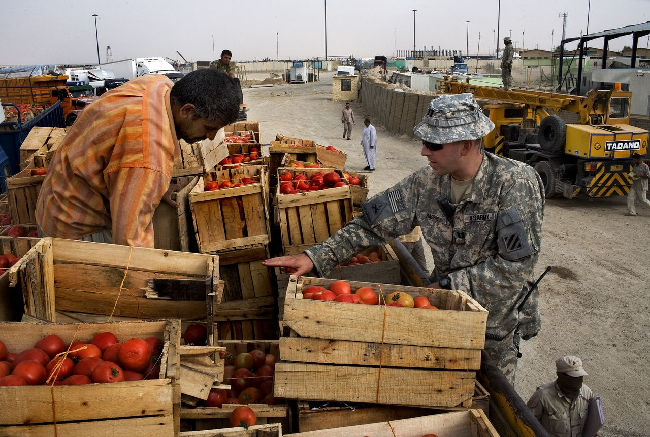 Een Amerikaanse militair zoekt naar wapens in een Iraakse vrachtwagen met tomaten bij de grenspost Zurbatiya, aan de grens tussen Iran en Irak. Foto Scott Nelson/WPN/HH A U.S. Army Border Transition Team (BTT) member searches an Iraqi tomato truck on Monday, October 1, 2007 at the Zurbatiya border crossing on the Iraq-Iran border in Wasit province. The U.S. military has stepped up monitoring at the crossing, an alleged transit point for weapons flowing in from Iran in recent months.
