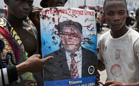 Caption: Opposition UDPS members hold up a blood-splattered poster of leader Etienne Tshisekedi after the presidential guard opened fire on the crowd outside N'Djili airport in Democratic Republic of Congo's capital Kinshasa November 26, 2011. Police in Congo blocked President Joseph Kabila's main rival Tshisekedi at an airport in Kinshasa on Saturday to stop him staging an election rally after at least two died in violence across the central African state's capital city. Two days before presidential and parliamentary elections, rival factions hurled rocks at each other and gunfire was heard across town.REUTERS/Finbarr O'Reilly (DEMOCRATIC REPUBLIC OF CONGO - Tags: POLITICS CIVIL UNREST)