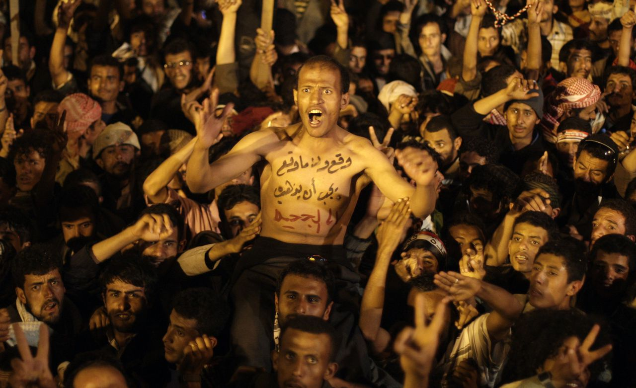 """A protestor, center, with writing Arabic on his chest that reads, """"whether he signed or not, he must go to hell,"""" celebrates with others for the signing by Yemeni President Ali Abdullah Saleh of a document agreeing to step down after a long-running uprising to oust him from 33 years in power in Sanaa, Yemen, Wednesday, Nov. 23, 2011. Yemen's authoritarian President Ali Abdullah Saleh agreed Wednesday to step down after a fierce uprising to oust him from 33 years in power. The U.S. and its powerful Gulf allies pressed for the deal, concerned that a security collapse in the impoverished Arab nation was allowing an active al-Qaida franchise to gain a firmer foothold. (AP Photo/Hani Mohammed)"""